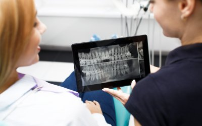 Two woman look at the tooth picture on a tablet at dentist office